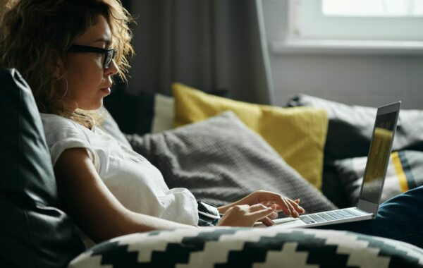 Woman sat at a Laptop on the Sofa