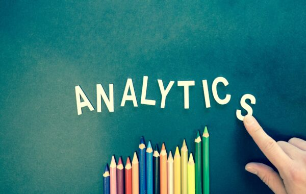 Analytics written in plastic letters above multi-coloured pencils
